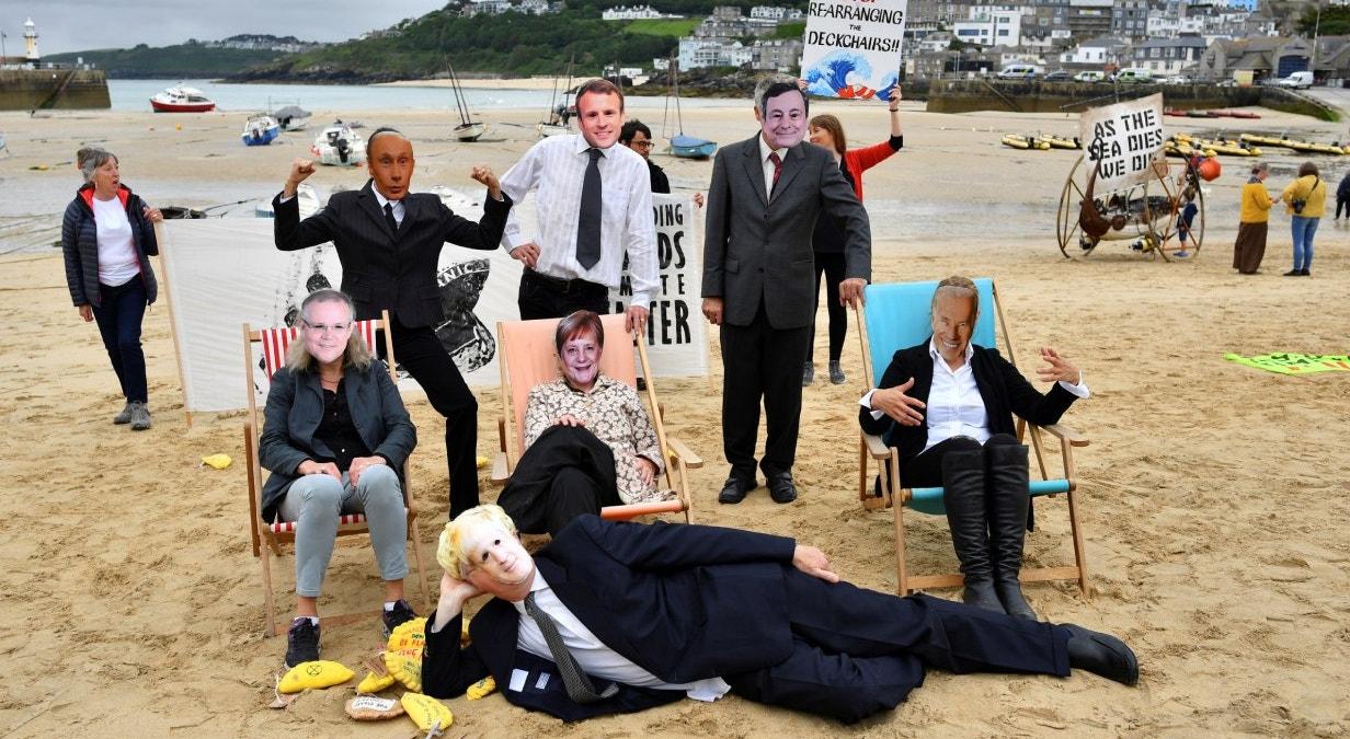 Ativistas climáticos usam máscaras representando líderes mundiais durante um protesto em St. Ives | Dylan Martinez - Reuters