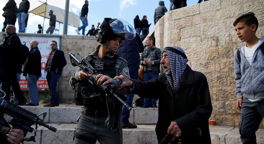 Um palestiniano discute com uma agente da polícia fronteiriça de Israel durante protestos na Cidade Velha de Jerusalém