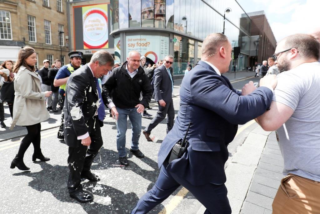 O líder do Brexit Party, Nigel Farage, caminha desgostosamente depois de ter sido atingido por um batido de iogurte quando chegava para um evento de campanha do Brexit Party em Newcastle. 20 maio 2019. REUTERS/Scott Heppell