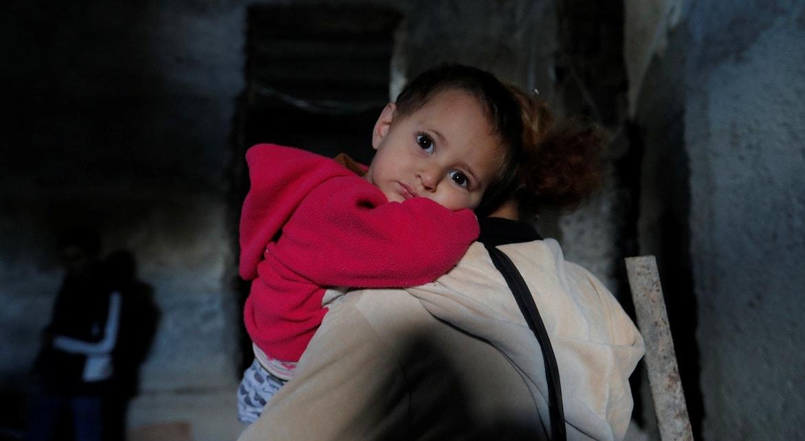 Mãe e filho a recolherem-se em abrigo   Reuters