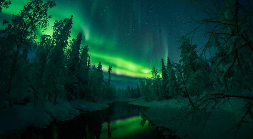 Aurora boreal vista por cima de Muonio na Lapónia, Finlandia
