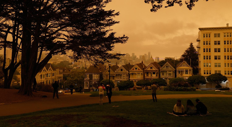 pessoas reúnem-se na Praça Alamo para observar o céu laranja com vista para The Painted Ladies em São Francisco, Califórnia. | John G.Mabanglo/EPA