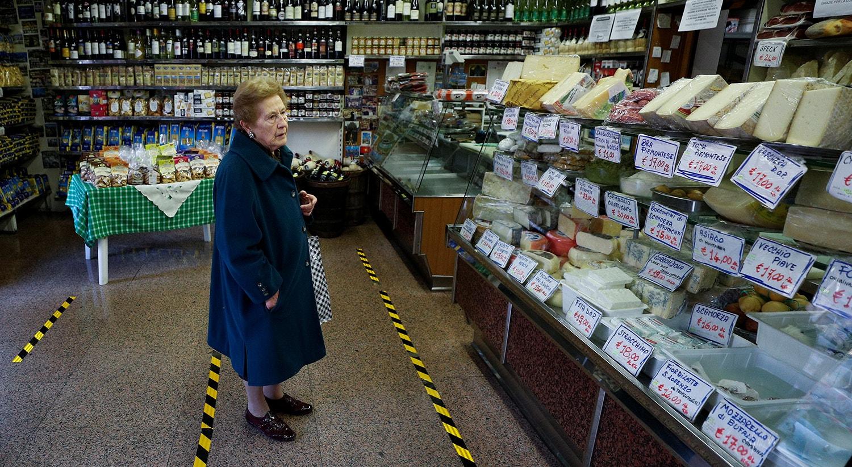 Uma senhora espera ser atendida atrás de linhas amareladas que marcam a distância que os clientes precisam manter entre eles dentro de um supermercado na área de Trastevere, em Roma /Guglielmo Mangiapane - Reuters
