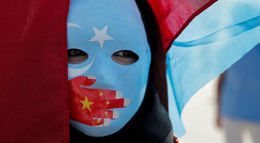 Um manifestante uigure usa uma máscara enquanto participa numa manifestação contra a China, em 2019