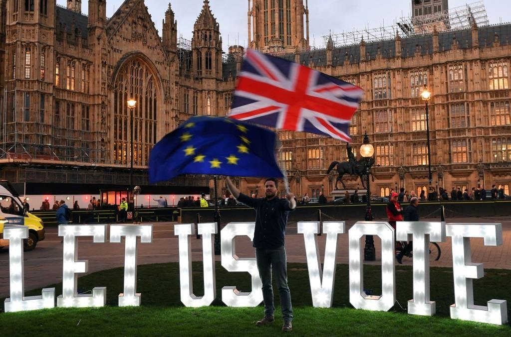 Um manifestante anti-Brexit agita bandeiras em frente às Parlamento em Londres. 27 março 2019. REUTERS/Dylan Martinez