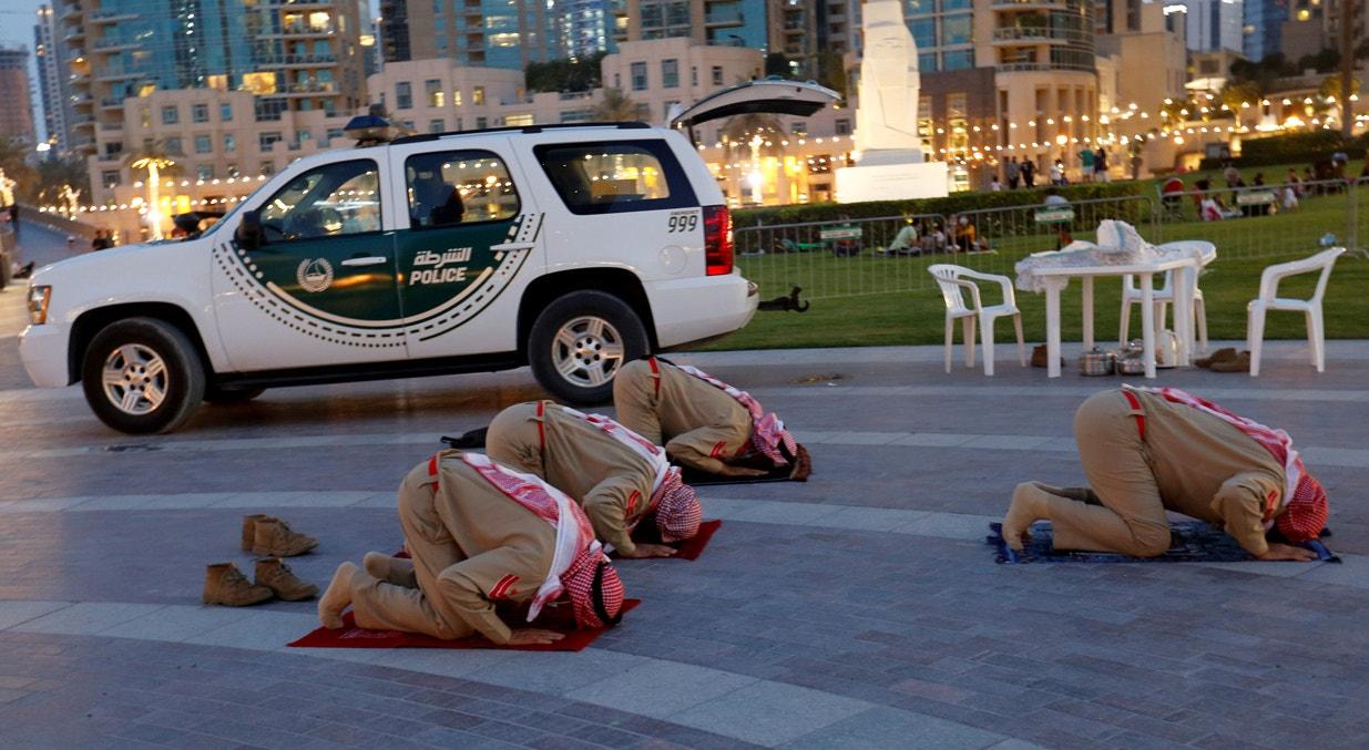 Emirados dos Árabes Unidos. Dubai. Polícia do emirado reza perto de zona comercial |Rula Rouhana - Reuters