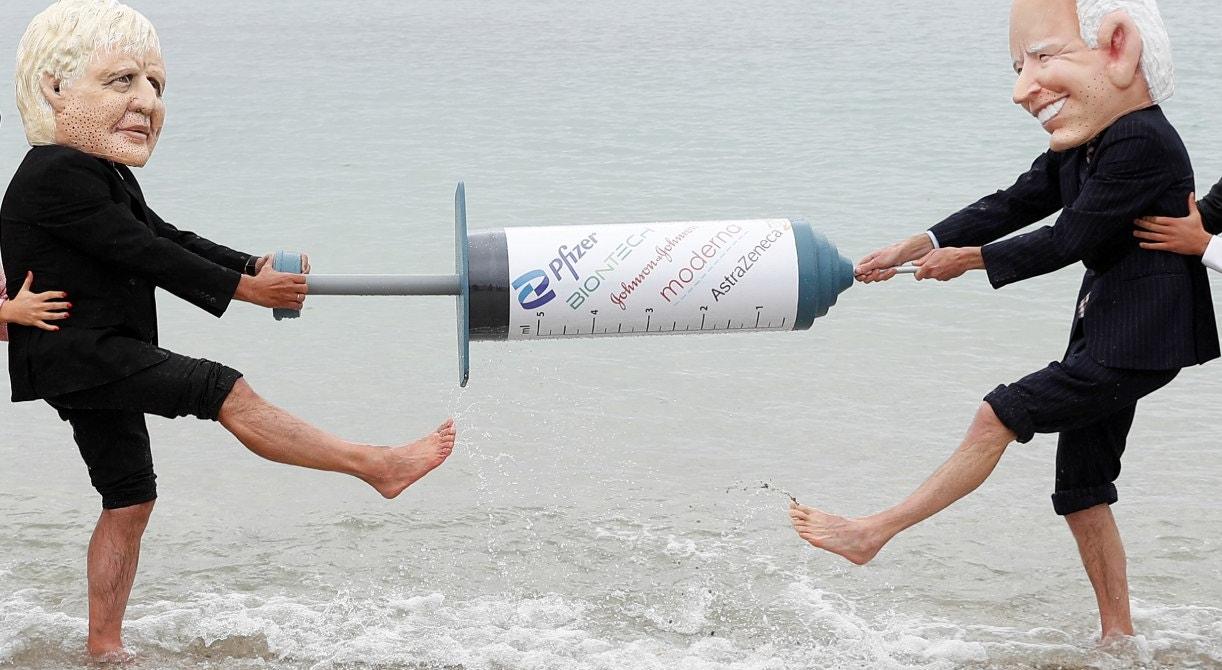 Ativistas da Oxfam com caricaturas de 'Cabeçudos' retratam o primeiro-ministro britânico Boris Johnson e o presidente dos EUA Joe Biden fingem lutar por uma vacina COVID-19, durante um protesto em uma praia perto de Falmouth, à margem da Cimeira dos G7Peter Nicholls - Reuters