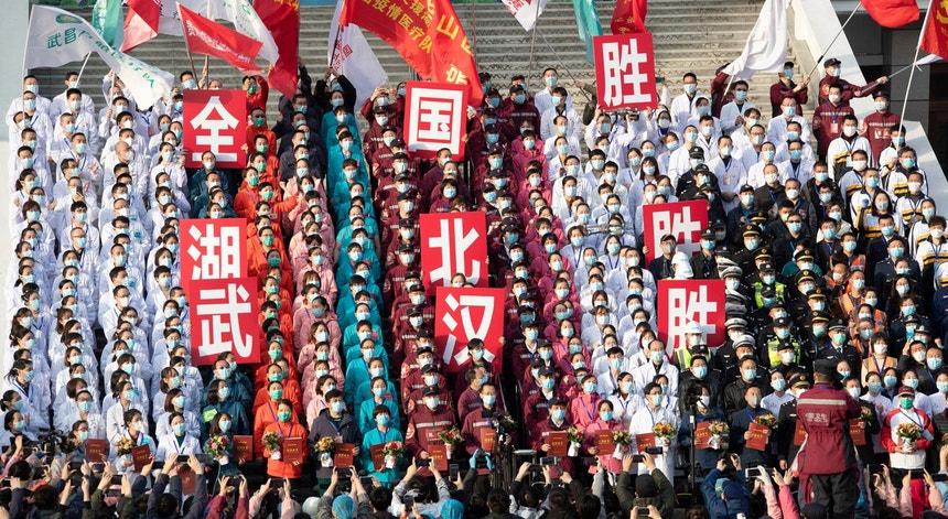 """Pessoal médico e de enfermagem, de máscara, posa para uma fotografia durante a cerimónia de encerramento do último hospital improvisado em Hubei, a 10 de março de 2020. As faixas dizem """"Vitória do país, vitória de Hubei, vitória de Wuhan"""""""