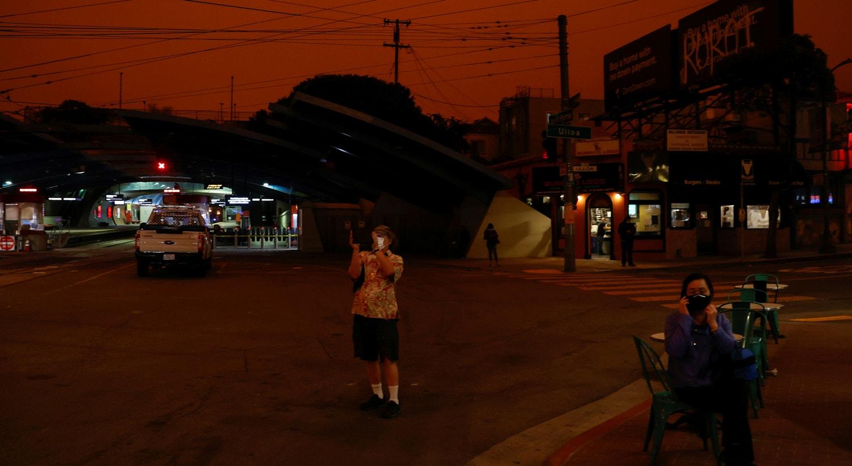 Uma pessoas fotográfa os céu laranja escurecido pelo fumo dos incêndios florestais da California em São Francisco. | Stephen Lam/Reuters