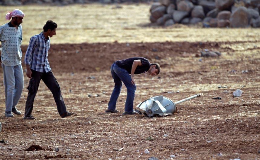 Homens inspeccionam os restos de um projetil russo, em Idlib, Síria Foto: Reuters