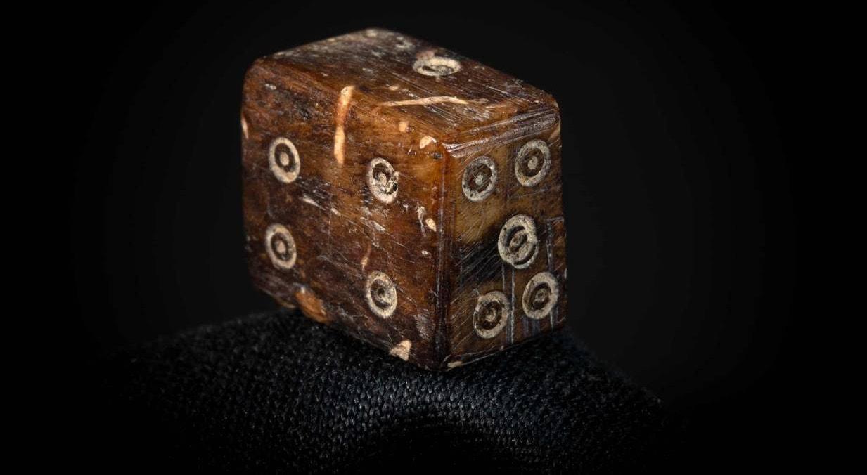 Dado romano de morfologia retangular, produzido em osso, encontrado na escavação da rua Ivens, 16, em Faro, entre as pedras de uma cloaca romana | Nuno de Santos Loureiro - barlavento