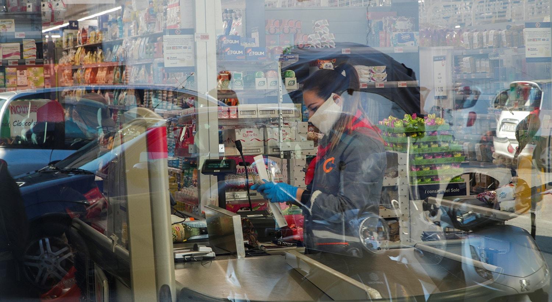 Operador de caixa com máscara de proteção em Nápoles /Ciro De Luca - Reuters