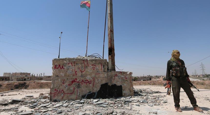 Um combatente curdo de pé com as suas armas perto de uma bandeira curda da região de Ghwairan, Síria.