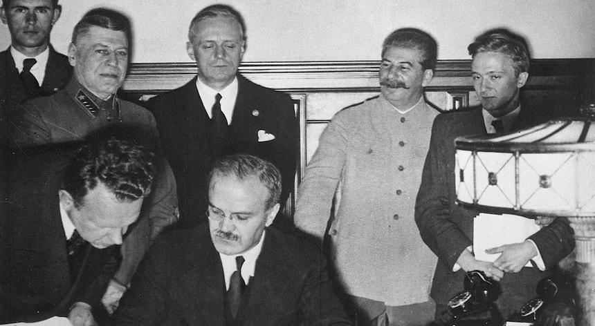 Molotov (ao centro, assinando o Pacto), Ribbentrop (atrás de Molotov) e Estaline (à dir. de Ribbentrop na fotografia)
